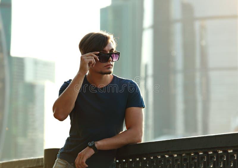 Jeune homme sexy posant dans des lunettes de soleil de mode sur la ville c de rue photo libre de droits