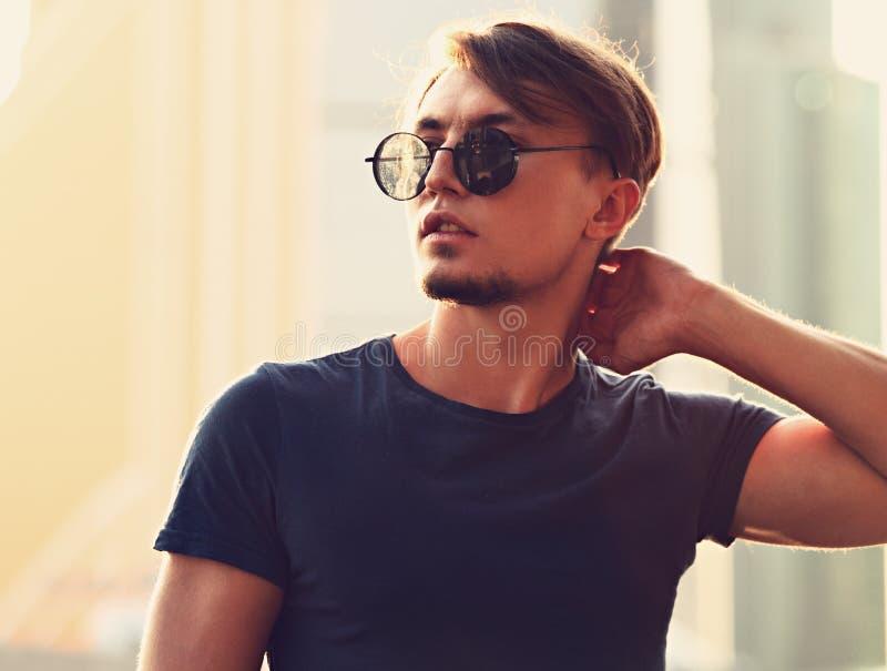 Jeune homme sexy posant dans des lunettes de soleil de mode sur la ville c de rue photos libres de droits