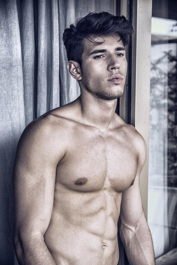 Jeune homme sexy se tenant sans chemise par des rideaux photos libres de droits