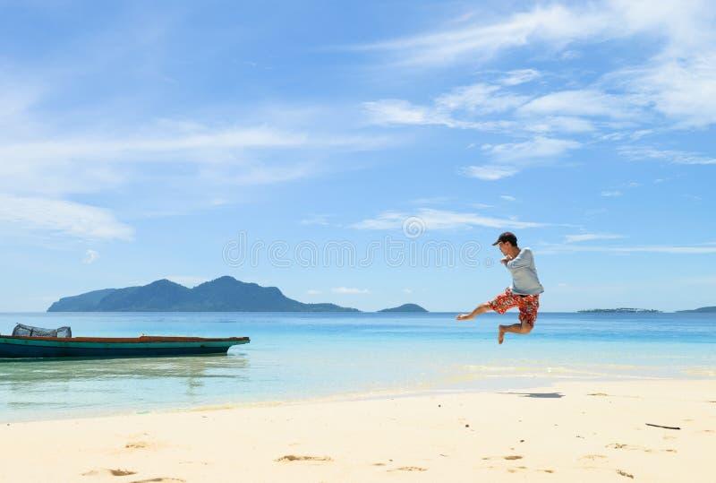 Jeune homme simple courant et sautant sur la plage blanche tropicale de sable image libre de droits