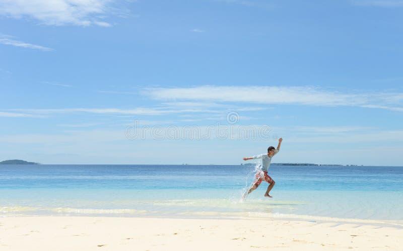 Jeune homme simple courant et sautant sur la plage blanche tropicale de sable images libres de droits