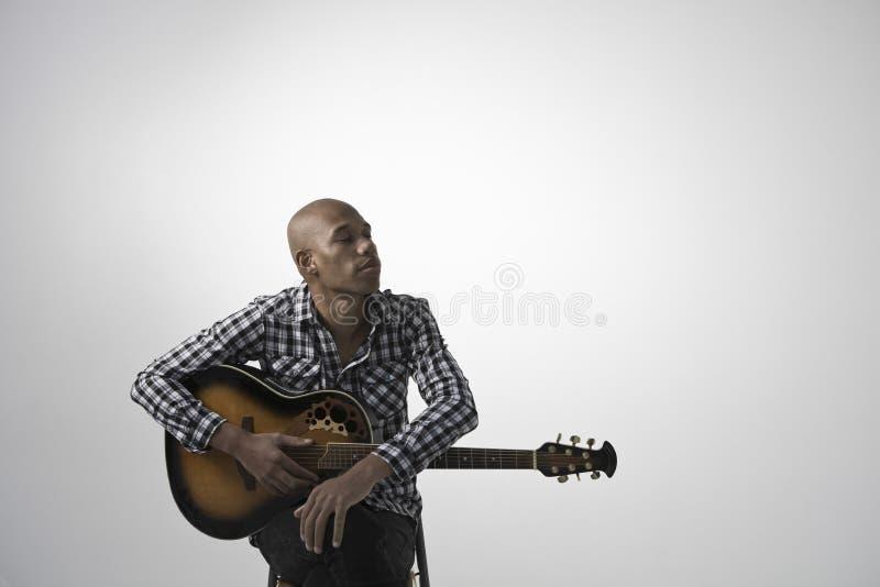 Jeune homme songeur avec la guitare photo stock