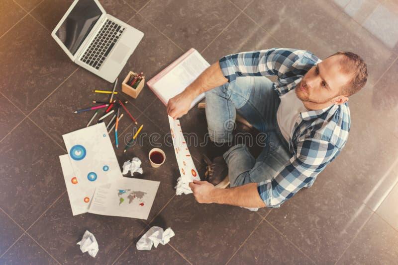 Jeune homme songeur travaillant dur sur le projet d'affaires photographie stock libre de droits