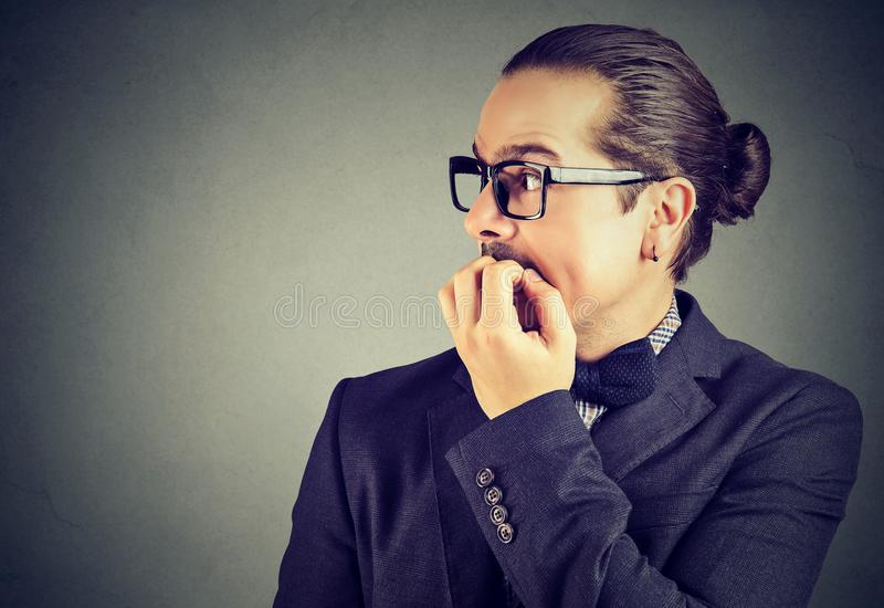 Jeune homme soucieux mordant ses ongles regardant au côté images stock
