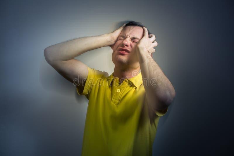 Jeune homme souffrant d'une attaque intense de mal de tête/migraine/inquiétude photographie stock libre de droits