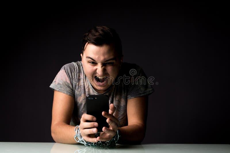 Jeune homme souffrant du cri perçant de dépendance de la dépendance de téléphone avec la chaîne sur des mains dans la chambre noi images stock