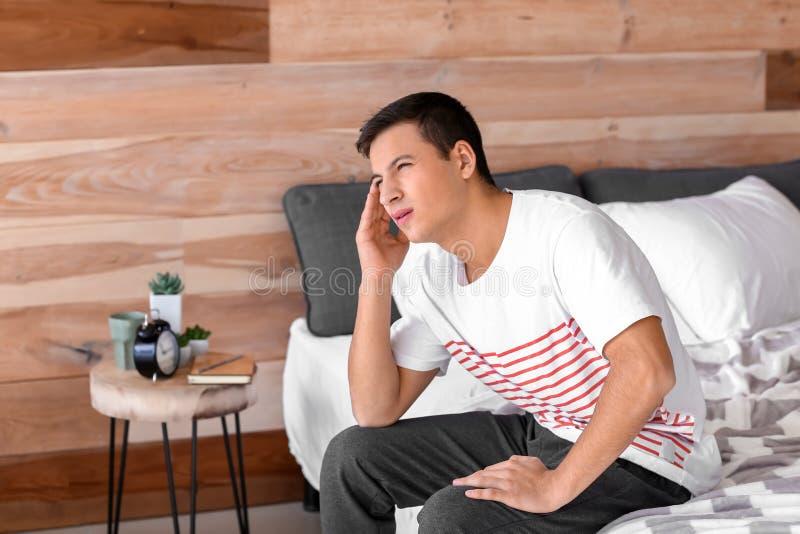 Jeune homme souffrant du mal de t?te ? la maison photo libre de droits