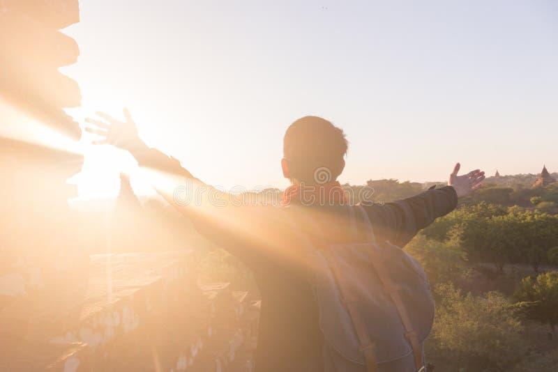 Jeune homme soulevant des mains contre la lumière du soleil - succès, accomplissement et victoire indiqués image stock