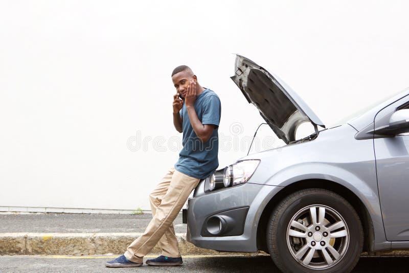 Jeune homme soumis à une contrainte réclamant l'aide au téléphone pour sa voiture cassée photographie stock libre de droits