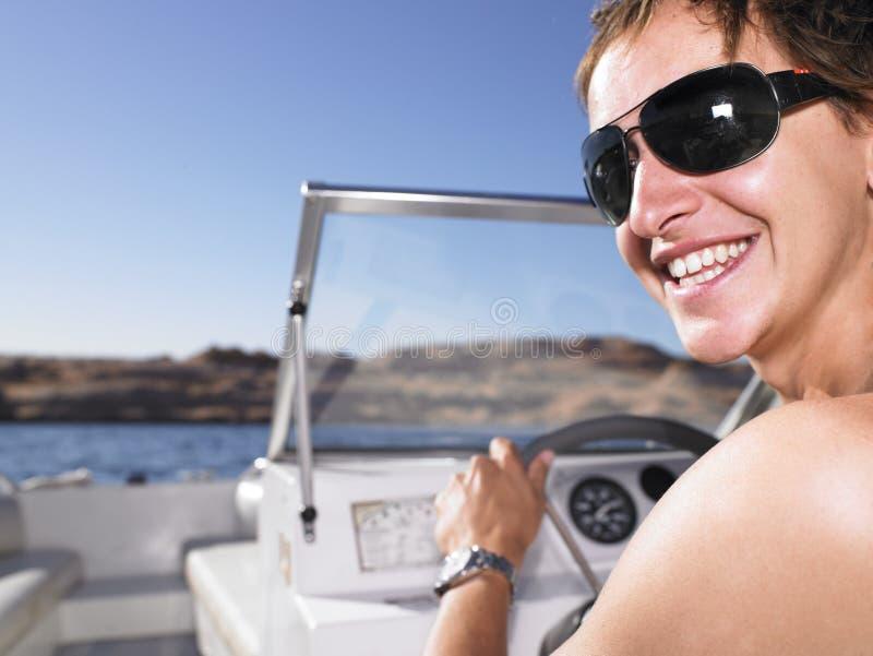Jeune homme souriant et conduisant le bateau photo stock