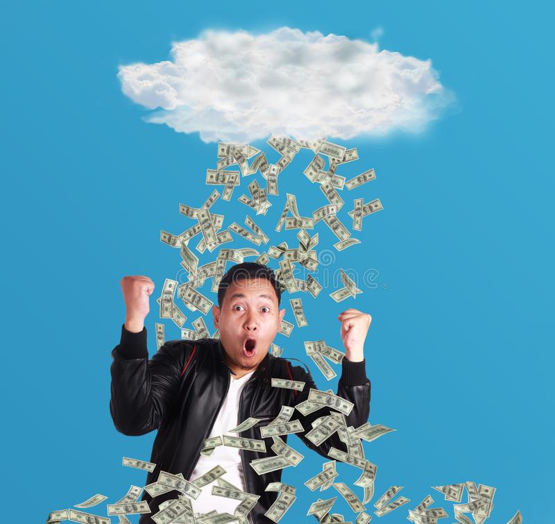 Jeune homme sous la pluie de l'argent photos stock