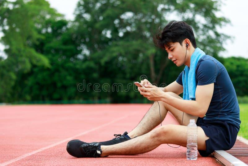 Jeune homme sportif asiatique s'asseyant et écoutant la musique photos stock