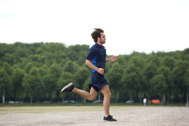 Jeune homme sportif courant dehors image libre de droits