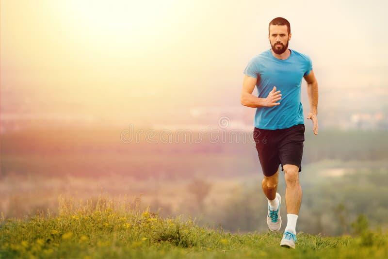 Jeune homme sportif courant pendant l'automne, matin d'hiver images stock