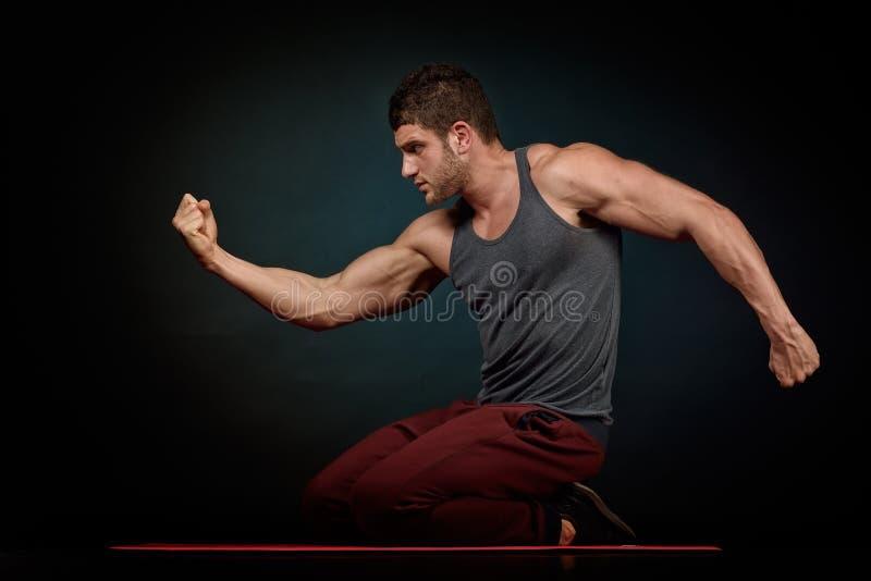 Download Jeune Homme Sportif Dans Le Studio Avec Le Fond Foncé Image stock - Image du lifestyle, muscles: 56476069