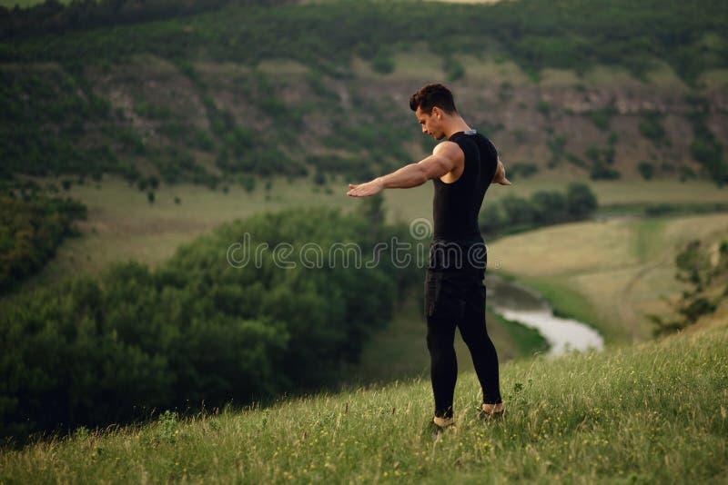 Jeune homme sportif dans les vêtements de sport faisant des exercices avec les mains augmentées et regardant vers le bas sur le f images libres de droits