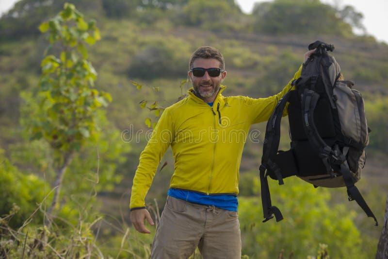 Jeune homme sportif heureux et attirant de randonneur avec le sac à dos de trekking augmentant à la fuite appréciante libre de vo images stock