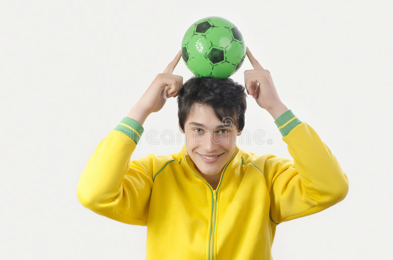 Jeune homme supportant une boule du football photos stock