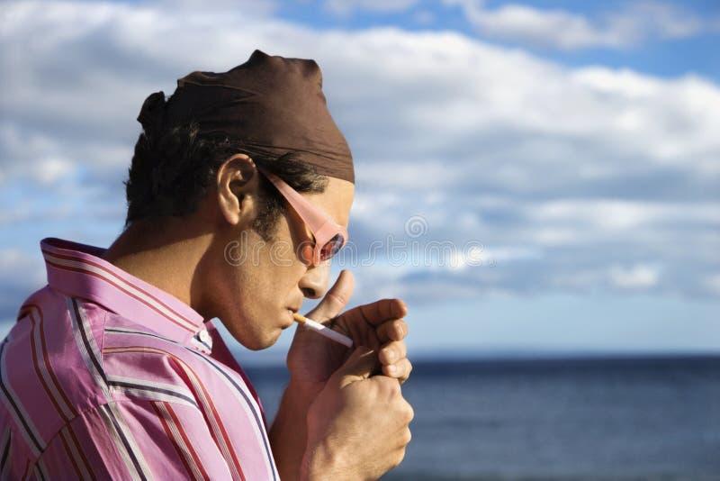 Jeune Homme Sur La Plage Allumant Une Cigarette Images libres de droits
