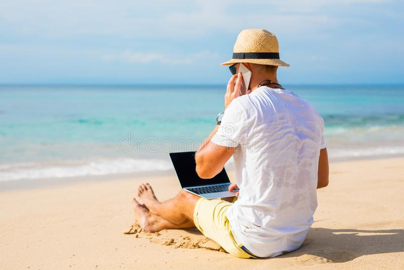 Jeune homme sur la plage fonctionnant avec l'ordinateur portable et parlant du téléphone photos libres de droits