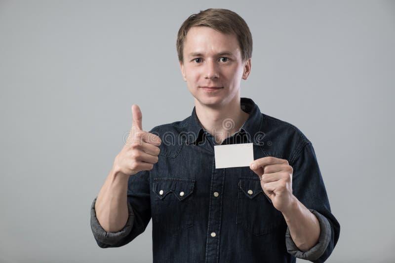 Jeune homme sur le gris photo stock