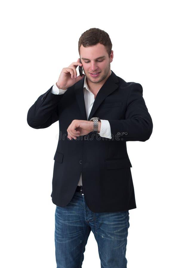 Jeune homme sur le ND de téléphone regardant la montre photos stock