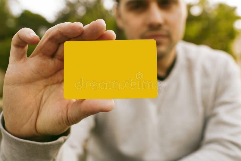 Jeune homme tenant l'avant jaune vide de carte de crédit de couleur du visage masculin r photos libres de droits