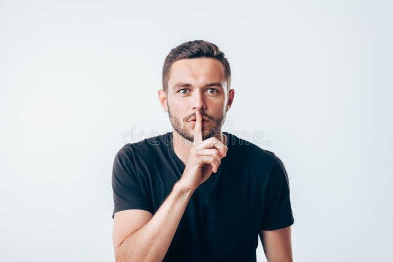 Jeune homme tenant l'index sur des lèvres demandant le silence images libres de droits
