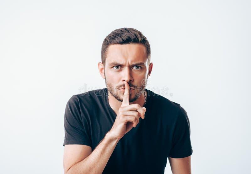 Jeune homme tenant l'index sur des lèvres demandant le silence photographie stock libre de droits