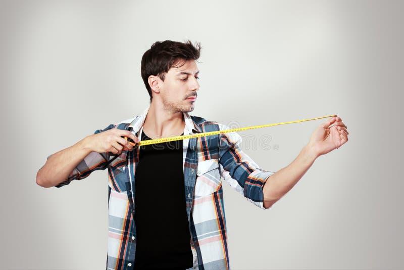 Jeune homme tenant la bande de mesure images stock