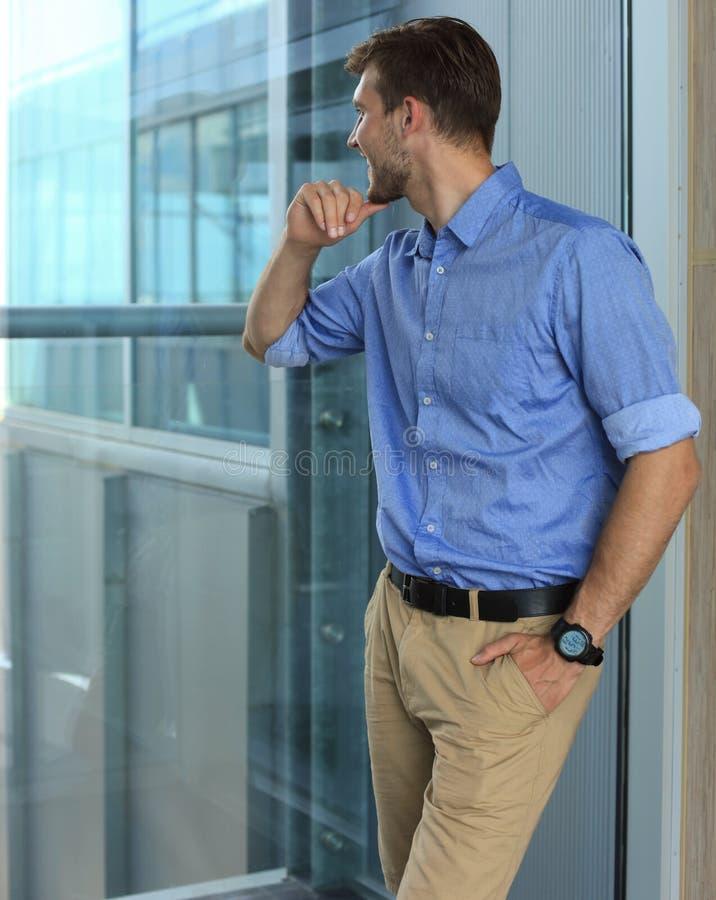 Jeune homme tenant la fenêtre proche dans son bureau tout en pensant à ses buts photo stock