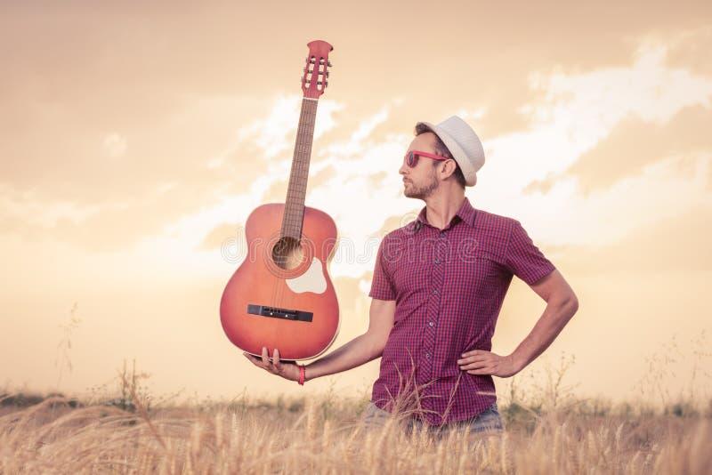 Jeune homme tenant la guitare sur le champ images stock