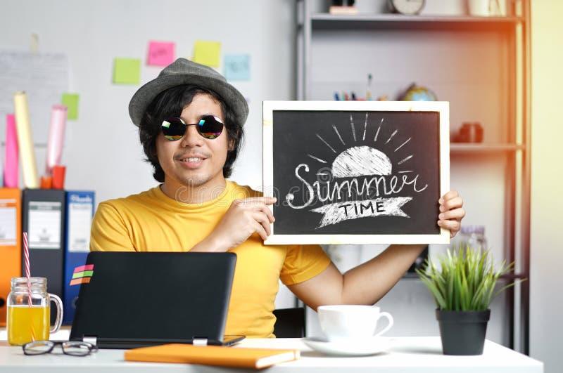 Jeune homme tenant la typographie d'heure d'été sur le tableau noir tandis que Wor image stock