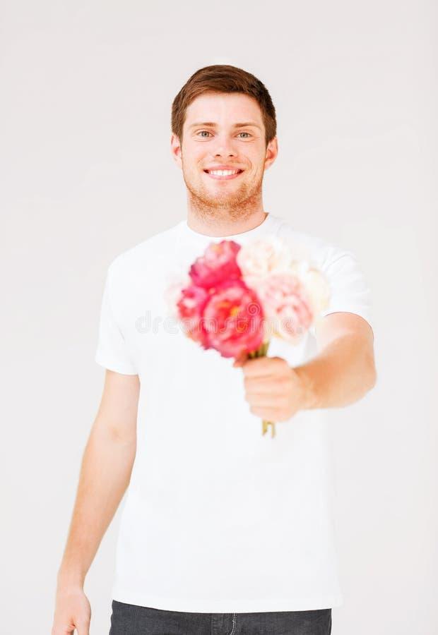 Jeune homme tenant le bouquet des fleurs photographie stock libre de droits
