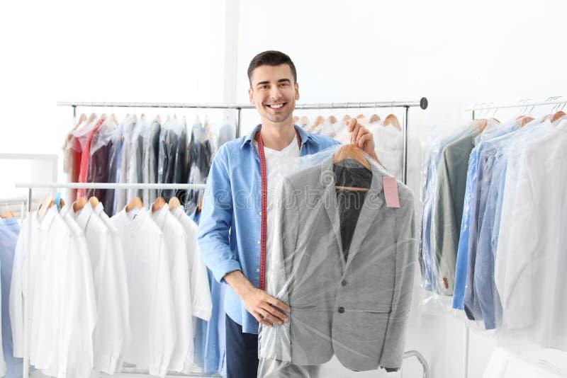 Jeune homme tenant le cintre avec la veste dans le sachet en plastique images stock