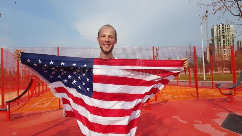 Jeune homme tenant le drapeau national américain photo stock