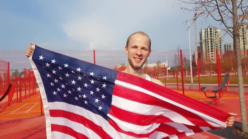 Jeune homme tenant le drapeau national américain photographie stock