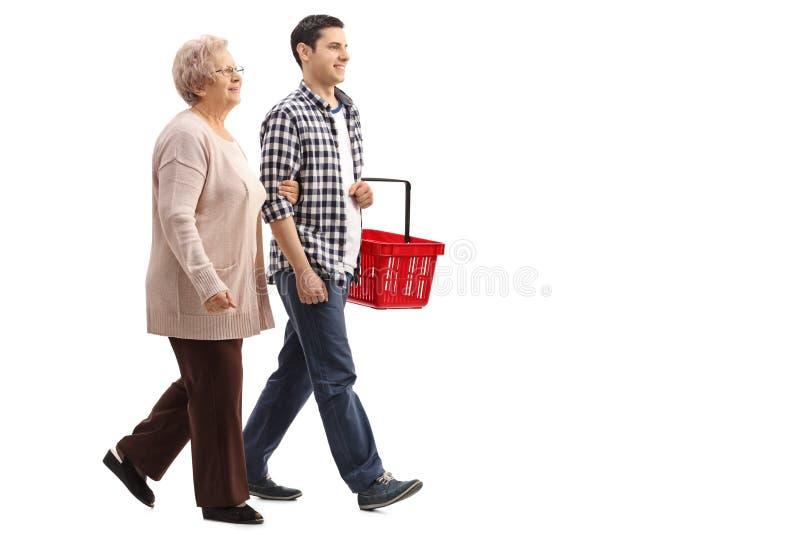 Jeune homme tenant le panier à provisions et marchant avec la femme mûre image stock
