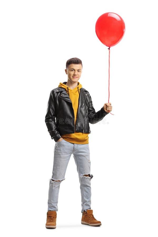 Jeune homme tenant un ballon rouge photographie stock libre de droits