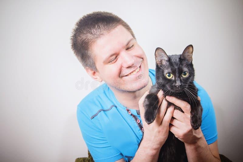 Jeune homme tenant un chat noir image libre de droits