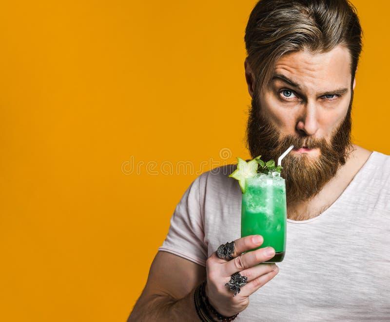 Jeune homme tenant un cocktail multicolore images stock