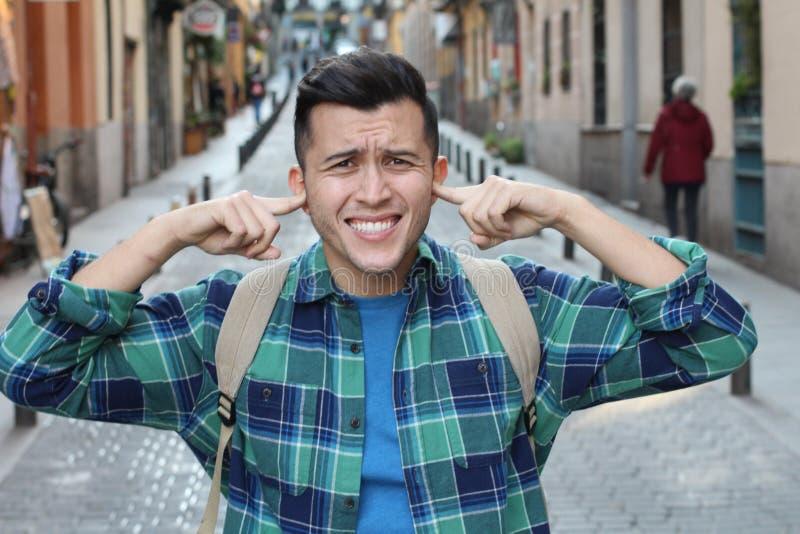 Jeune homme traitant des bruits insupportables image libre de droits