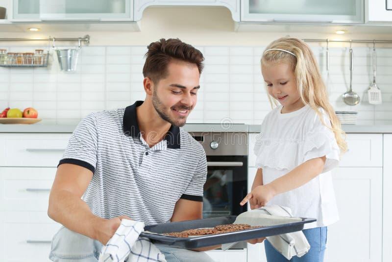 Jeune homme traitant sa fille avec les biscuits cuits au four cuits au four par four fait maison photo stock