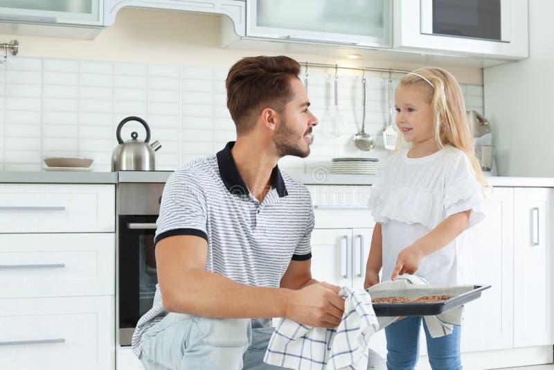 Jeune homme traitant sa fille avec les biscuits cuits au four cuits au four par four fait maison photographie stock