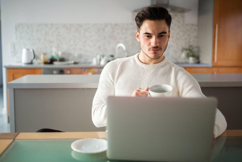 Jeune homme travaillant à la maison sur le carnet photographie stock
