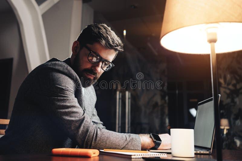 Jeune homme travaillant au bureau moderne de nuit Fond brouillé Directeur barbu employant le bloc-notes d'ordinateur portable et  photos libres de droits