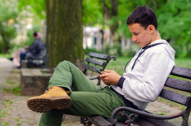 Jeune homme travaillant au dispositif de protection en parc photo stock