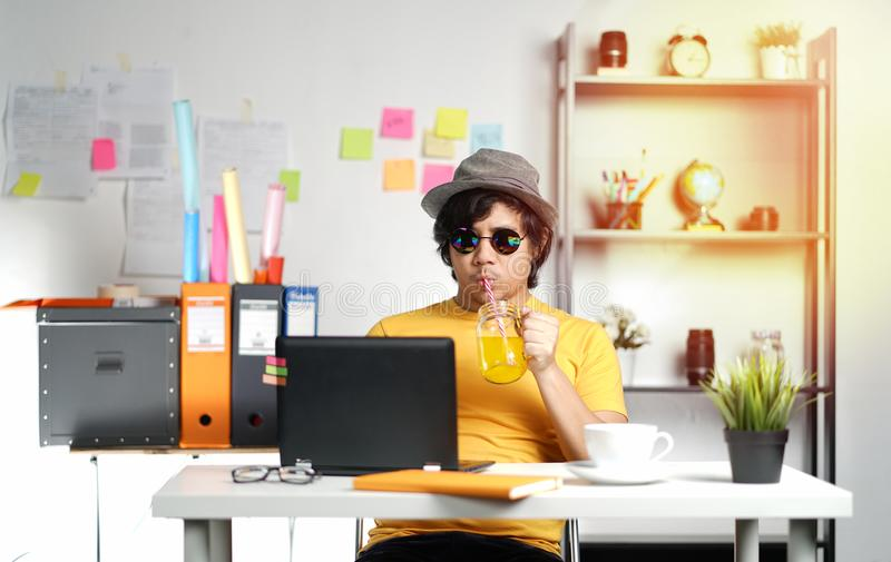 Jeune homme travaillant avec l'ordinateur portable et le jus d'orange potable sur Summe images libres de droits