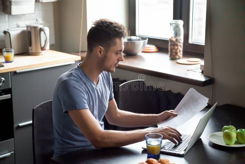 Jeune homme travaillant avec l'ordinateur portable tout en prenant le petit déjeuner à la maison photo libre de droits