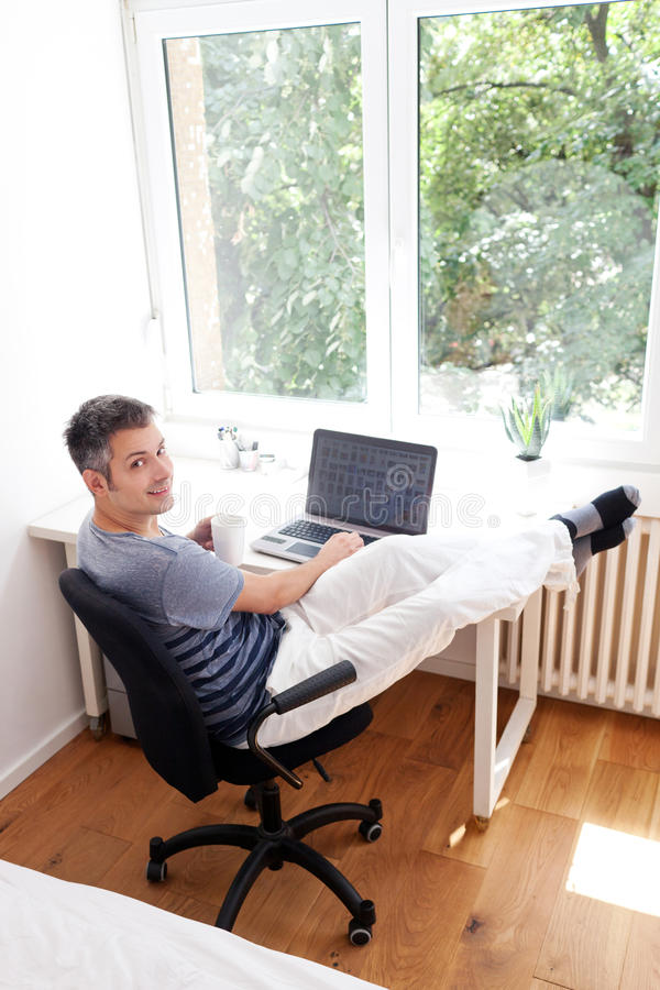 Jeune homme travaillant sur l'ordinateur portable photographie stock